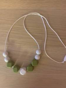 Bilde av SMÅROLLING ammesmykke oliven-white