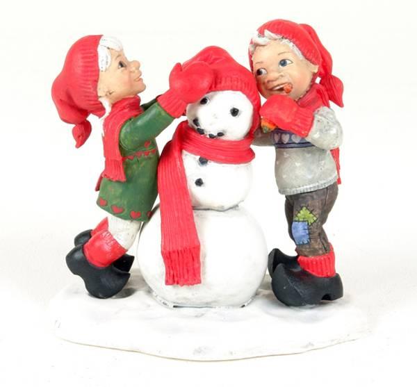 Jente og gutt lager snømann