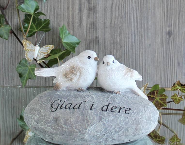 Gravpynt. To hvite fugler på stein med teksten